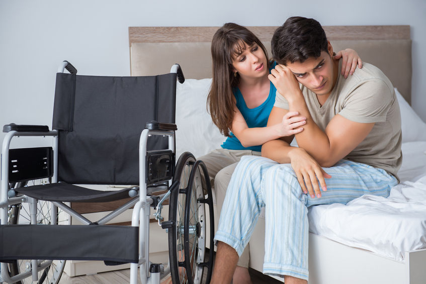 woman consoling young man in wheelchair